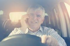 Zakenman die een telefoon met behulp van, die in auto zitten Stock Afbeeldingen