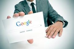 Zakenman die een uithangbord met de Google-onderzoekshomepage houden Royalty-vrije Stock Afbeeldingen