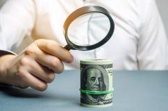 Zakenman die een vergrootglas over de dollars houden Analyse van inkomen en winsten Het concept het vinden van bronnen van royalty-vrije stock foto's
