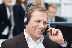 Zakenman die een vraag op een hoofdtelefoon nemen Stock Foto