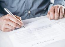 Zakenman die een wettelijk document ondertekenen Stock Foto's