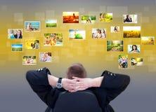 Zakenman die en de beelden van de fotogalerij situeren bekijken Stock Afbeeldingen