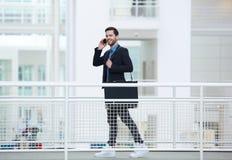 Zakenman die en op mobiele telefoon lopen spreken Royalty-vrije Stock Foto