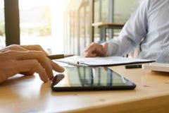 Zakenman die en tablet samenwerken gebruiken op een modern kantoor stock foto