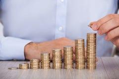Zakenman die euro muntstukken stapelen bij bureau Stock Afbeelding
