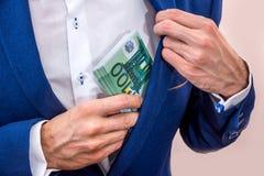 Zakenman die 100 euro rekeningen zetten Stock Afbeeldingen