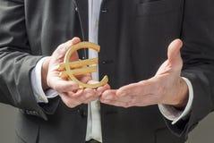Zakenman die Euro symbool houden stock afbeelding