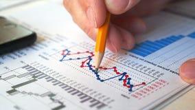 Zakenman die financieel verslag en grafieken in het bureau controleren op het werk stock footage