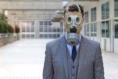 Zakenman die gasmasker in bureauruimte dragen stock afbeelding