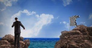 Zakenman die gecontroleerde vlag op rots tegen hemel bekijken Stock Foto's