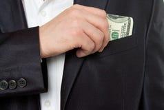 Zakenman die geld in zakkostuum zet Stock Afbeelding
