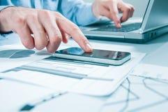 Zakenman die generische ontwerplaptop werken Wat betreft het schermsmartphone Interface de wereldwijd van de verbindingstechnolog Stock Foto's