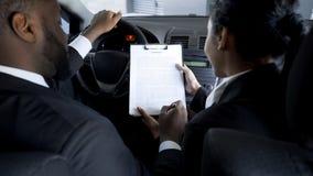 Zakenman die gewaagd contract met vrouwelijke partner in auto, schaduwzaken ondertekenen stock afbeelding