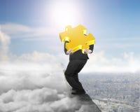 Zakenman die gouden puzzel op rand met cloudscape dragen Royalty-vrije Stock Fotografie