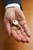 Zakenman die gouden sleutel houden stock foto