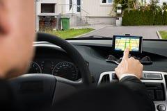 Zakenman die gps navigatiesysteem in auto met behulp van royalty-vrije stock afbeelding