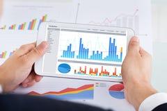 Zakenman die grafieken op digitale tablet vergelijken bij bureau Stock Foto