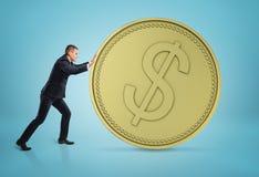 Zakenman die groot gouden dollarmuntstuk rollen Stock Foto's