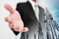 Zakenman die hand, met de dubbele torens van de blootstellingstelecommunicatie met TV-antennes en satellietschotel uitbreiden royalty-vrije stock foto