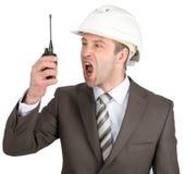 Zakenman die in helm bij walkie-talkie gillen royalty-vrije stock afbeelding