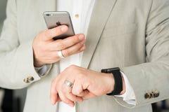 Zakenman die het Apple-Horloge en Apple gebruiken stock afbeelding