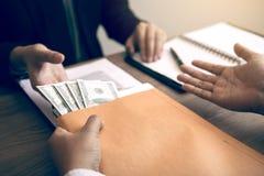 Zakenman die in het geheim een steekpenning geven door geldrekeningen in het document van het envelopcontract te geven stock fotografie