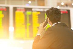 Zakenman die het tijdschema van de luchthavenvlucht bekijken royalty-vrije stock foto