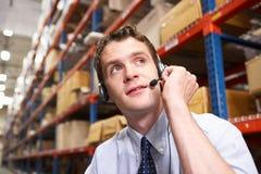 Zakenman die Hoofdtelefoon in het Pakhuis van de Distributie met behulp van royalty-vrije stock afbeeldingen