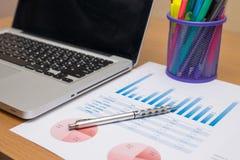 Zakenman die investeringsgrafieken met laptop analyseren Stock Afbeelding