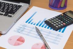Zakenman die investeringsgrafieken met laptop analyseren Stock Foto's