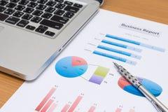 Zakenman die investeringsgrafieken met laptop analyseren Stock Foto