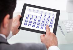 Zakenman die kalender op digitale tablet bekijken Royalty-vrije Stock Afbeeldingen