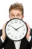 Zakenman die klok houden stock foto