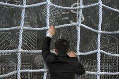 Zakenman die kruiselingse kabel netto op bedrijfsconceptendoo beklimmen royalty-vrije stock foto's