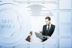 Zakenman die laptop binnen bankkluis met behulp van Stock Afbeeldingen