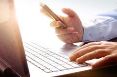 Zakenman die laptop en mobiele telefoon met behulp van Stock Foto's