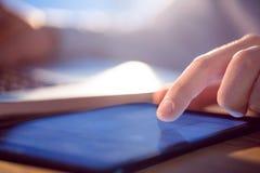 Zakenman die laptop en tablet gebruiken bij bureau Stock Afbeeldingen