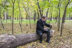 Zakenman die laptop in het park hebben in de herfst Een mens werkt bij een computer in het park royalty-vrije stock afbeeldingen