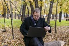 Zakenman die laptop in het park hebben in de herfst Jonge mensenzitting op boom in park met laptop op zijn overlapping en control royalty-vrije stock afbeeldingen