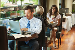 Zakenman die laptop in koffie met behulp van Stock Afbeeldingen