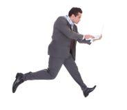 Zakenman die laptop met behulp van terwijl het lopen Royalty-vrije Stock Foto's