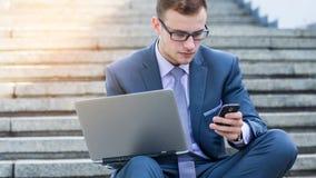 Zakenman die laptop PC en mobiele telefoon met behulp van. Hij zit op treden. Stock Foto