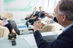 Zakenman die met collega's in vergaderzaal bespreken royalty-vrije stock afbeeldingen