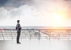 Zakenman die met koffie op zijn balkon van de mening genieten Stock Afbeeldingen