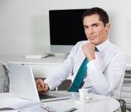 Zakenman die met laptop in bureau werkt Stock Afbeelding