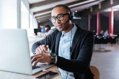Zakenman die met laptop werken die hoofdtelefoons en microfoon met behulp van Stock Fotografie
