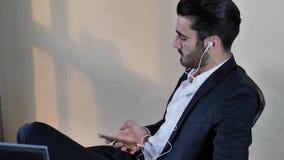 Zakenman die met oortelefoons aan muziek luisteren stock footage