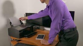 Zakenman die met printer in het bureau werken stock footage