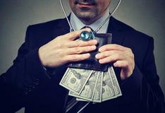 Zakenman die met stethoscoop aan portefeuille met dollarbankbiljetten luisteren Stock Afbeelding