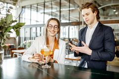Zakenman die met vrouw bij de bar flirten stock fotografie
